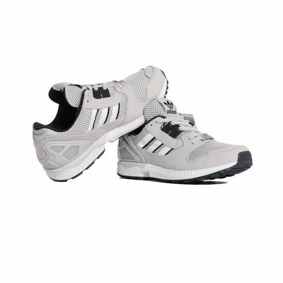 کفش اسپرت و ورزشی ادیداس طوسی و مشکی مخصوص دویدن مردانه با رویه توسی روشن که پا چپ به لبه پا راست تکیه داده