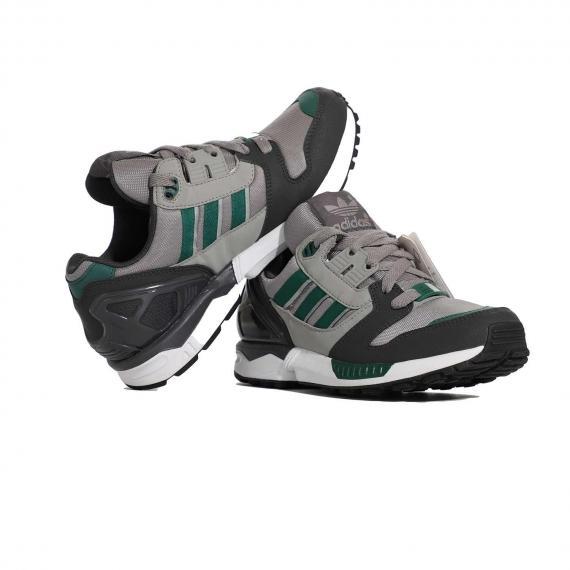 کفش ادیداس طوسی و سیاه با لایه میانی پای راست روی پای چپ از بغل