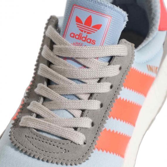 کفش ورزشی بندی ادیداس اینیکی رانر با بندهای طوسی و زبانه ابی روشن با برچسب نارنجی نام adidas بر آن از نما نزدیک