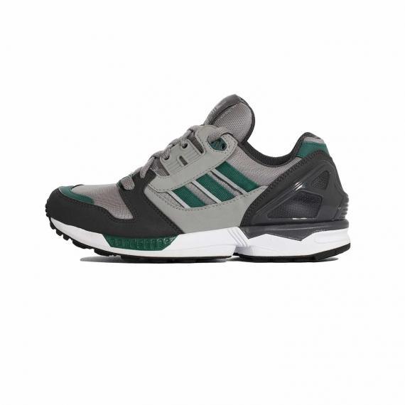 کفش ادیداس طوسی و مشکی با خط های سبز بیرون پای چپ از بغل