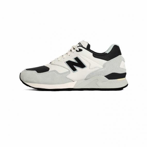 کفش ورزشی نیو بالانس رانینگ مشکی، طوسی و سفید با زیره لاستیکی مشکی و حرف N در کناره کتانی همراه با درج نام New Balance بر زبانه سفید