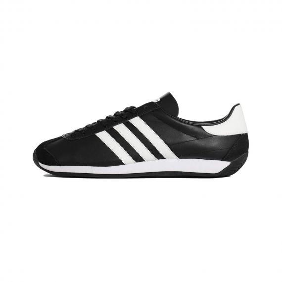 کفش کلاسیک بندی آدیداس از جنس چرم مشکی همراه با 3 خط سفید در کناره های کفش، زیره لاستیکی سفید و تکه چرم سفید در پشت پاشنه