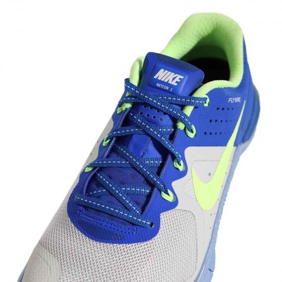 کفش اسپرت بندی زنانه با بندهای آبی و قلابهای سبز فلای وایر با رویه توری طوسی و نام Nike Metcon2 بر روی زبانه