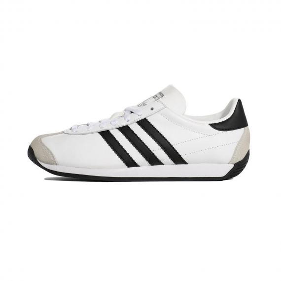 کفش پیاده روی ادیداس مدل کانتری با رویه سفید و 3 خط مشکی در کناره کفش و دو قسمت جیر کرم رنگ در جلو پنچه و پشت پاشنه و درج نام Adidas بر زبانه