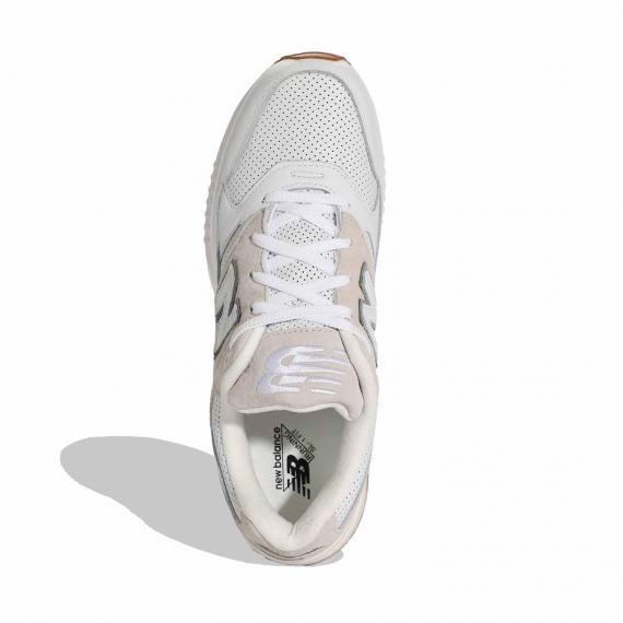 کفش نیوبالانس با رویه مشبک چرمی سفید و جیر کرم مخصوص پای پنجه دار و درج نام new balance در داخل پاشنه از نمای ایستاده پای چپ