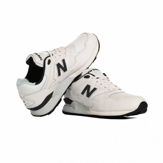 کتانی اسپرت و ورزشی نیوبالانس اصل با رویه مشبک تنفس پذیر که پای چپ روی پای راست تکیه داده است