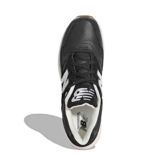 کفش طبی مخصوص خار پاشنه نیو بالانس با رویه جنس چرم مشکی و کفش نرم از نمای روبه روی پای چپ ایستاده