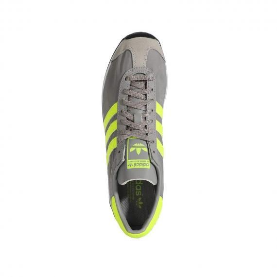 کتونی چرمی طوسی ادیداس مخصوص پیاده روی و رانینگ دارای سیستم گردش هوا برای جلوگیری از بوی بد پا از نمای روبه روی کتانی پای چپ ایستاده