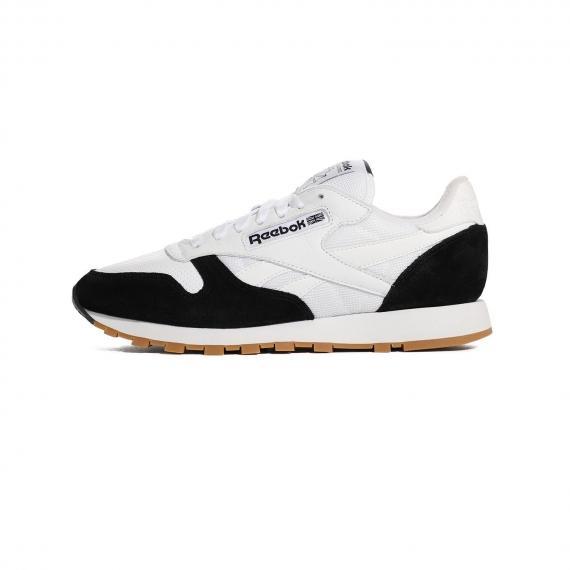 کتانی ریبوک کلاسیک با رویه مش سفید و جیر مشکی، زیره سفید به همراه نام برند ریباک روی کناره کفش