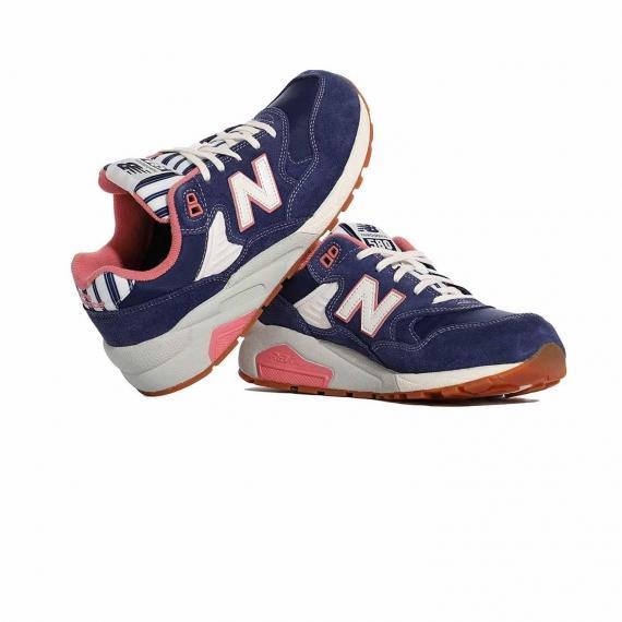 کفش ورزشی بنفش صورتی زنانه نیوبالانس مخصوص رانینگ بسیار با کیفیت که پا چپ رو لبه پا راست تکیه داده