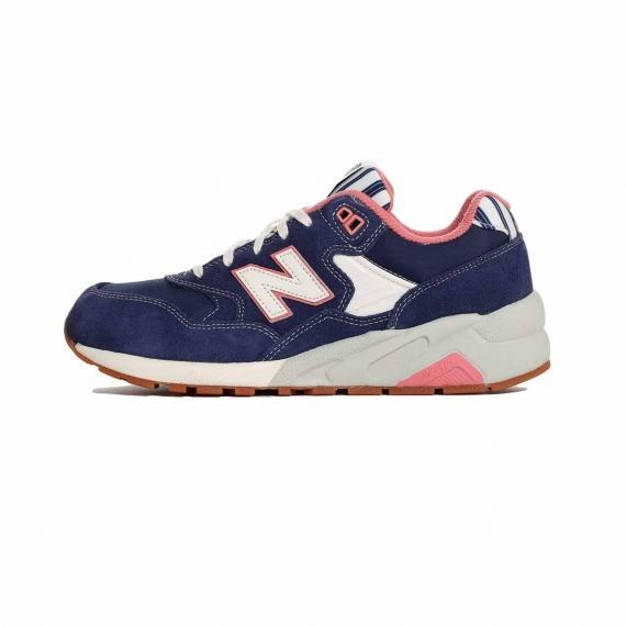 کفش نیو بالانس دخترانه بنفش و صورتی رنگ مخصوص پیاده روی با لایه میانی طوسی و سفید، نماد N سفید و نام تکنولوژی رولایت در کنارههای کفش