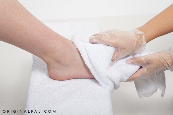 خسک کردن پا با حوله سفید برای کاهش رطوبت و اجاد قارچ انگشتان پا