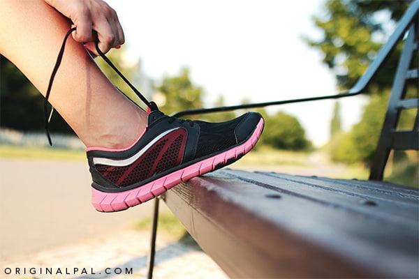 ورزشکاری در حال بستن بند کفش مخصوص دویدن مشکی بر روی صندلی پارک