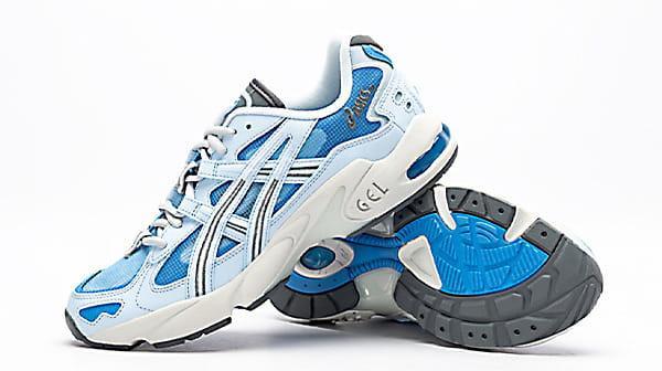 کفش ورزشی اصل اسیکس همراه با لوگوی Asics در کناره کتانی که پای چپ به زیره پای راست تکیه داده است