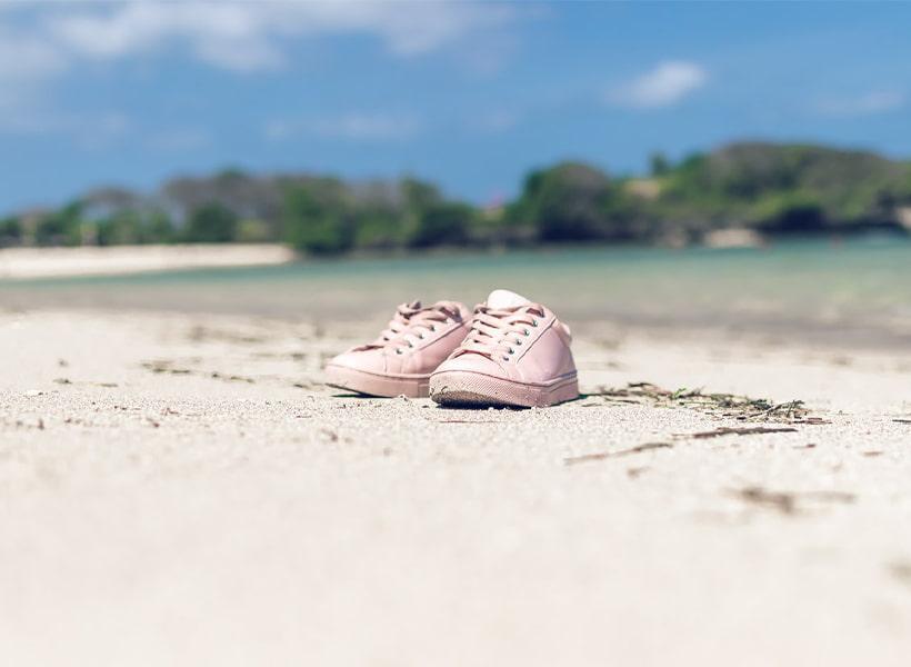 کفش اسپرت زنانه صورتی بر روی ساحل در کنار دریا در فصل گرم تابستان