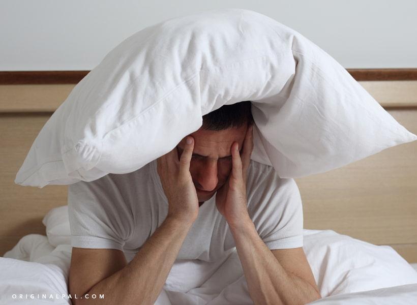 مردی در رخت خواب که دستان خود را بر روی صورتش گرفته و بالش روی سرش قرار دارد