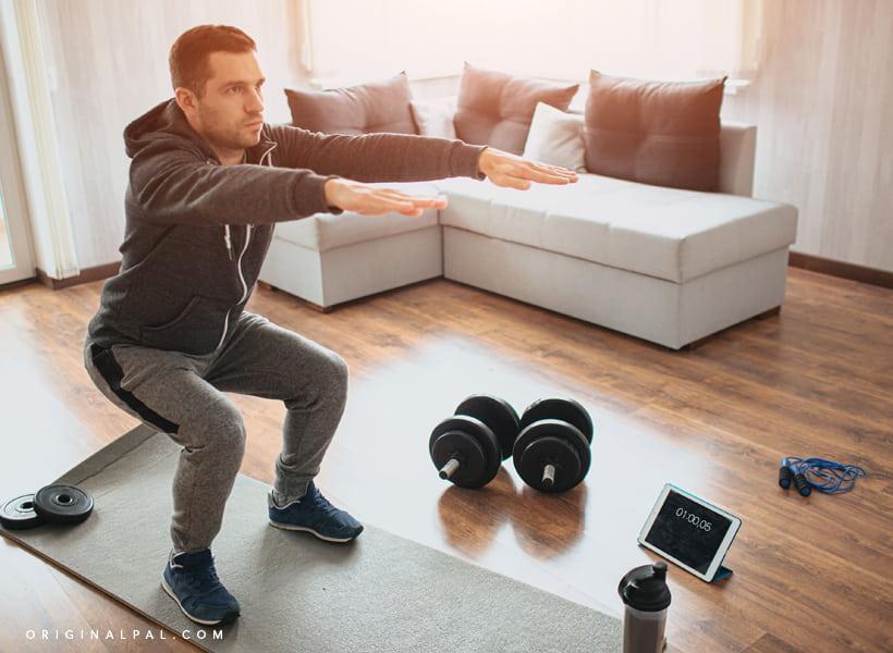 مردی در حال ورزش در فضای خانه با دمبل و تبلت و طناب ورزشی که روی زمین هستند