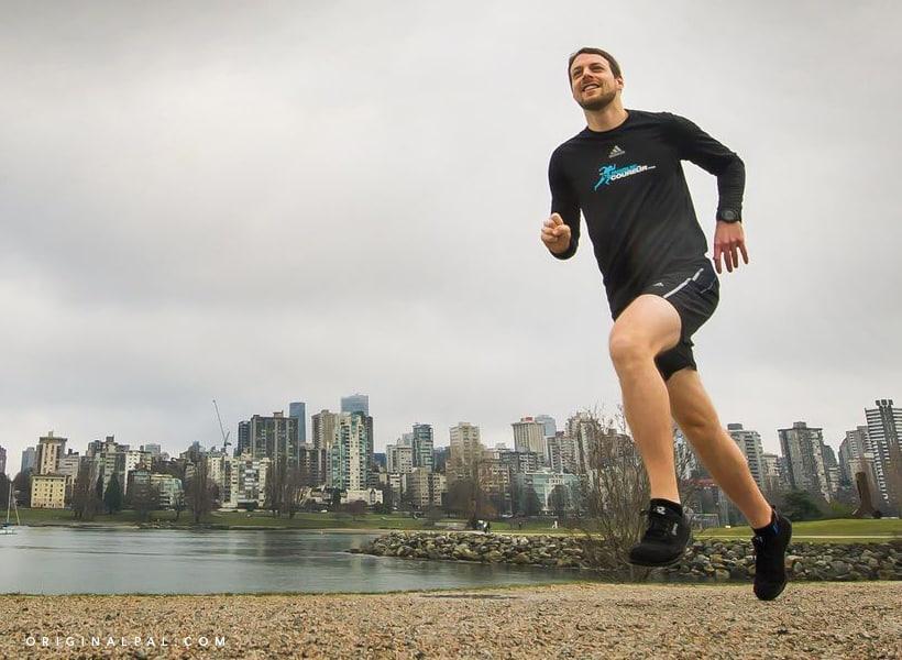 آقای در حال دویدن در فضای آزاد کنار دریاچه که پشتش ساختمان های زیادی وجود دارد