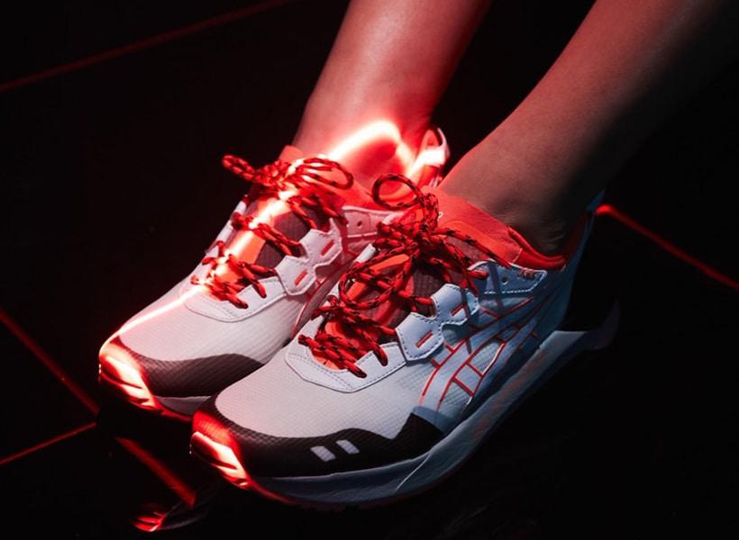 کفش آسیکس ژل لایت سفید و نارنجی با بندهای نارنجی که خط خط های مشکی دارد و یک نور روی کفش افتاده