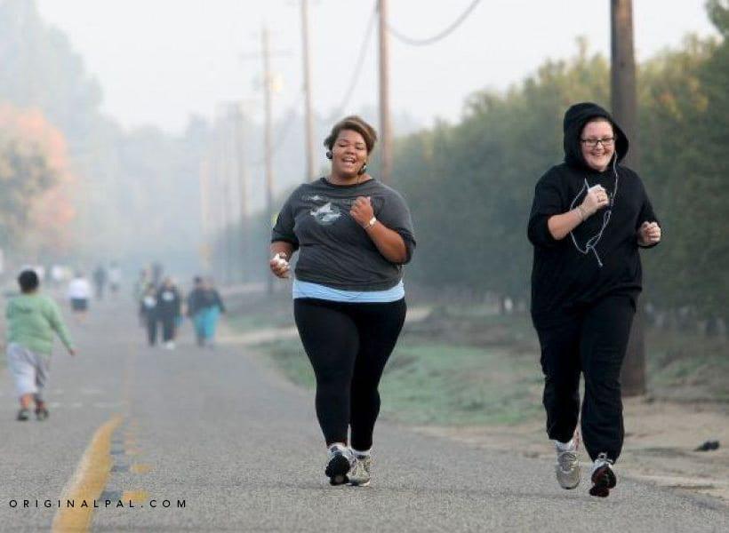 یک زن سیاه پوست و یک زن سفید پوست در حال دویدن در خیابان برای کم کردن وزن