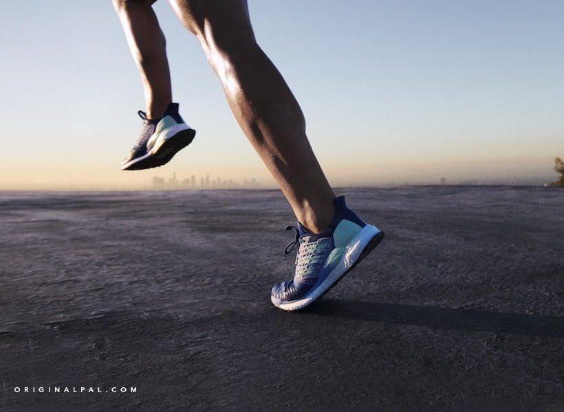 عکس دو پای یک مرد در حال دویدن روی زمین سیمانی با کفش اسپرت