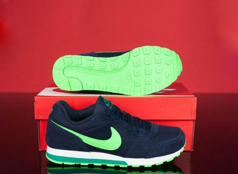 کفش اسیکس ورزشی سورمه ای با زیره سبز فسفری روی جعبه قرمز