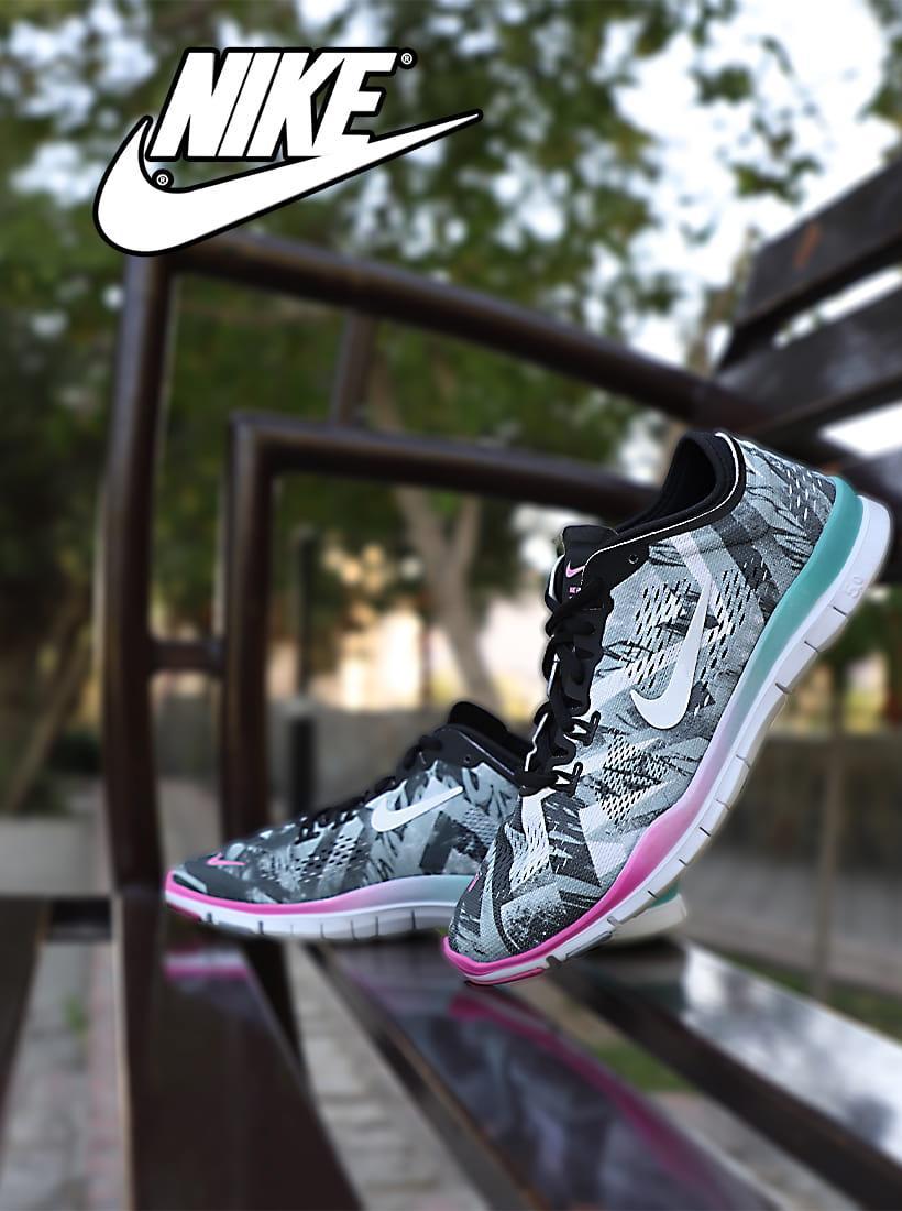 کفش ورزشی نایک دخترانه و زنانه رنگی مناسب برای دویدن و پیاده روی با بندهای مشکی و زیره طبی که پاشنه پای چپ تکیه داده به صندلی آهنی و در کنار پای راست روی صندلی قرار گرفته است